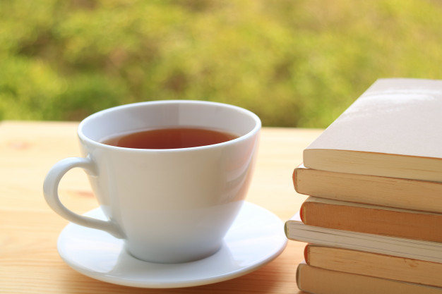 cup-hot-tea-with-pile-books-wooden-table-with-blurred-background-plants-garden_76000-481